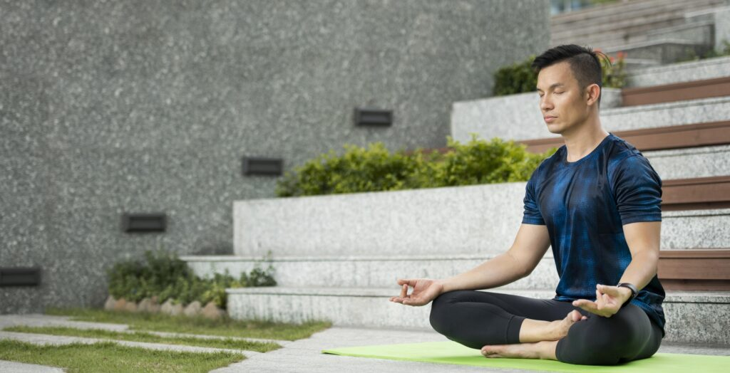 man-practicing-yoga-outdoors-with-copy-space