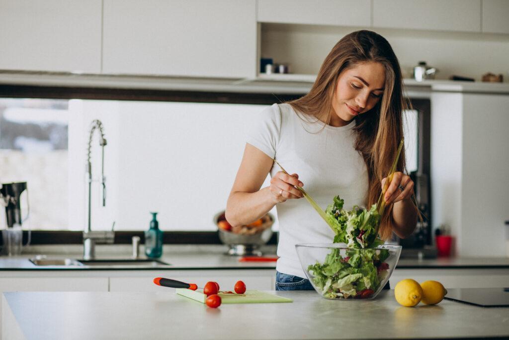 Young woman making salad at the kitchen